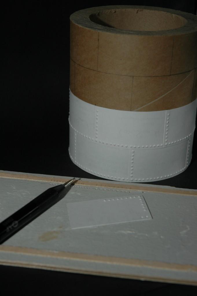 """Værktøjet som bruges til at præge """"nitterne"""" i kartonstykkerne."""