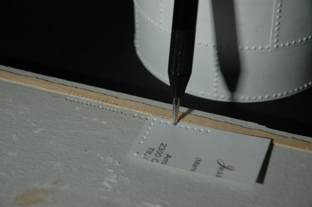 """Billedet viser hvordan man trykker kartonen ned i de små huller med den kugleformede spids og derved danner en """"nitte"""""""