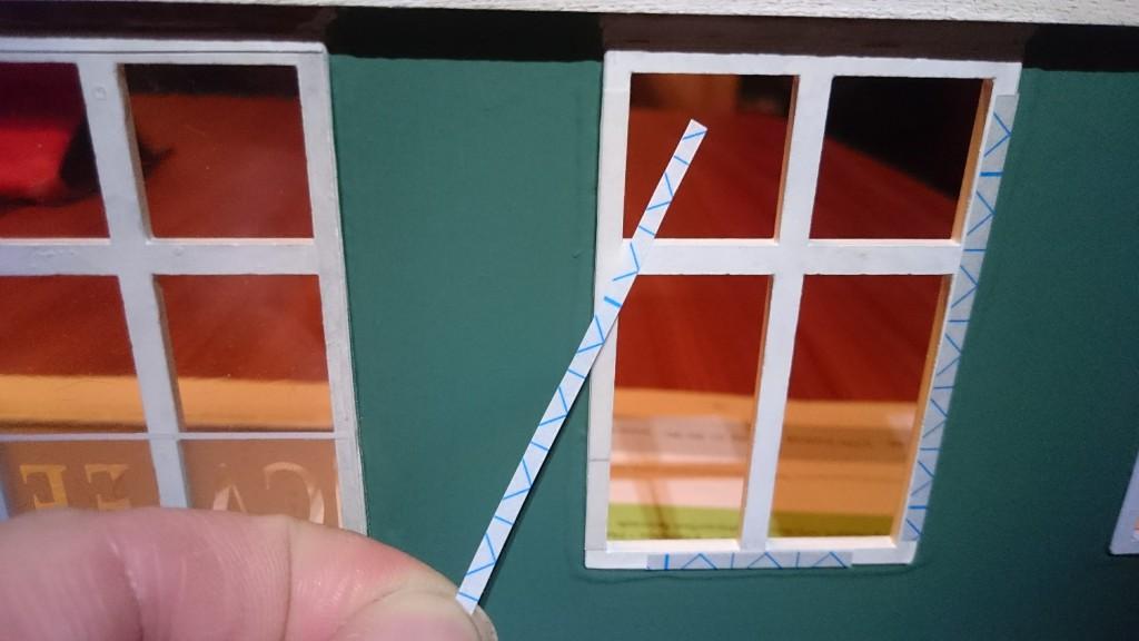 """Jeg bruger smalle strimler af tynd dobbeltklæbende tape til at montere """"glasset""""."""