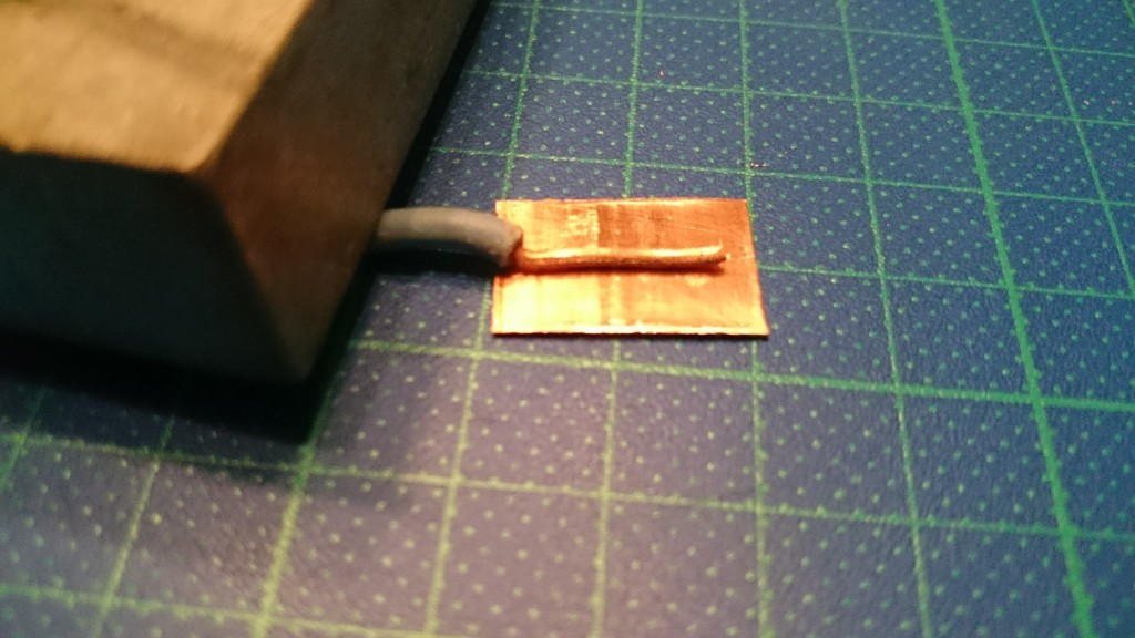 Herefter tapes en ledning fast på bagsiden af emnet